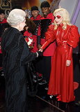 To meet Queen Elizabeth, Lady Gaga opted for a Victorian-inspired red leather dress with a high collar — and sparkling eye makeup to match.