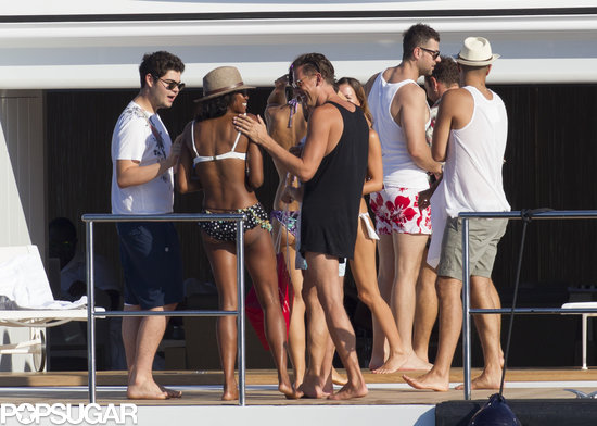 Naomi Campbell chatted with a large group of male friends.