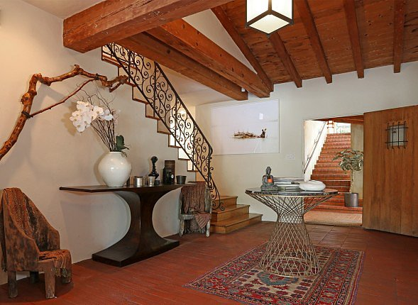 Inside the foyer, wooden ceiling beams, warm tile floors, and an iron railing pay homage to the home's Spanish Revival architecture.