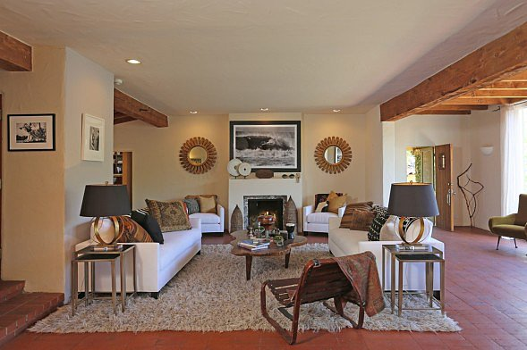 In the den, a cozy rug anchors the seating area, conveniently located next to the fireplace.