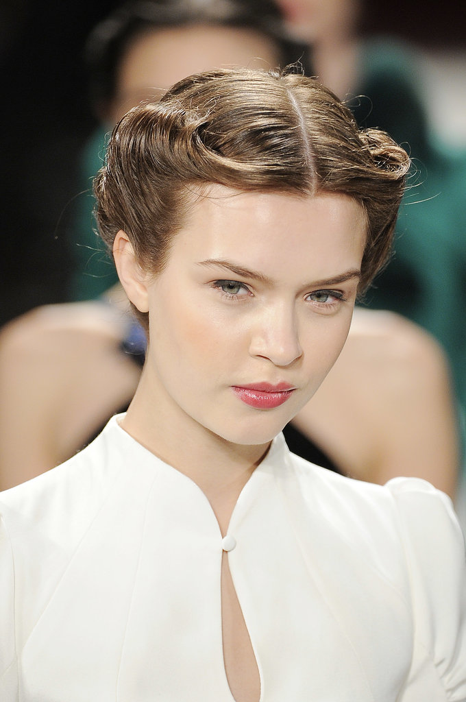 A chic '40s-style rolled updo kept the hair off the face of models in the Carolina Herrera Autumn 2013 show.