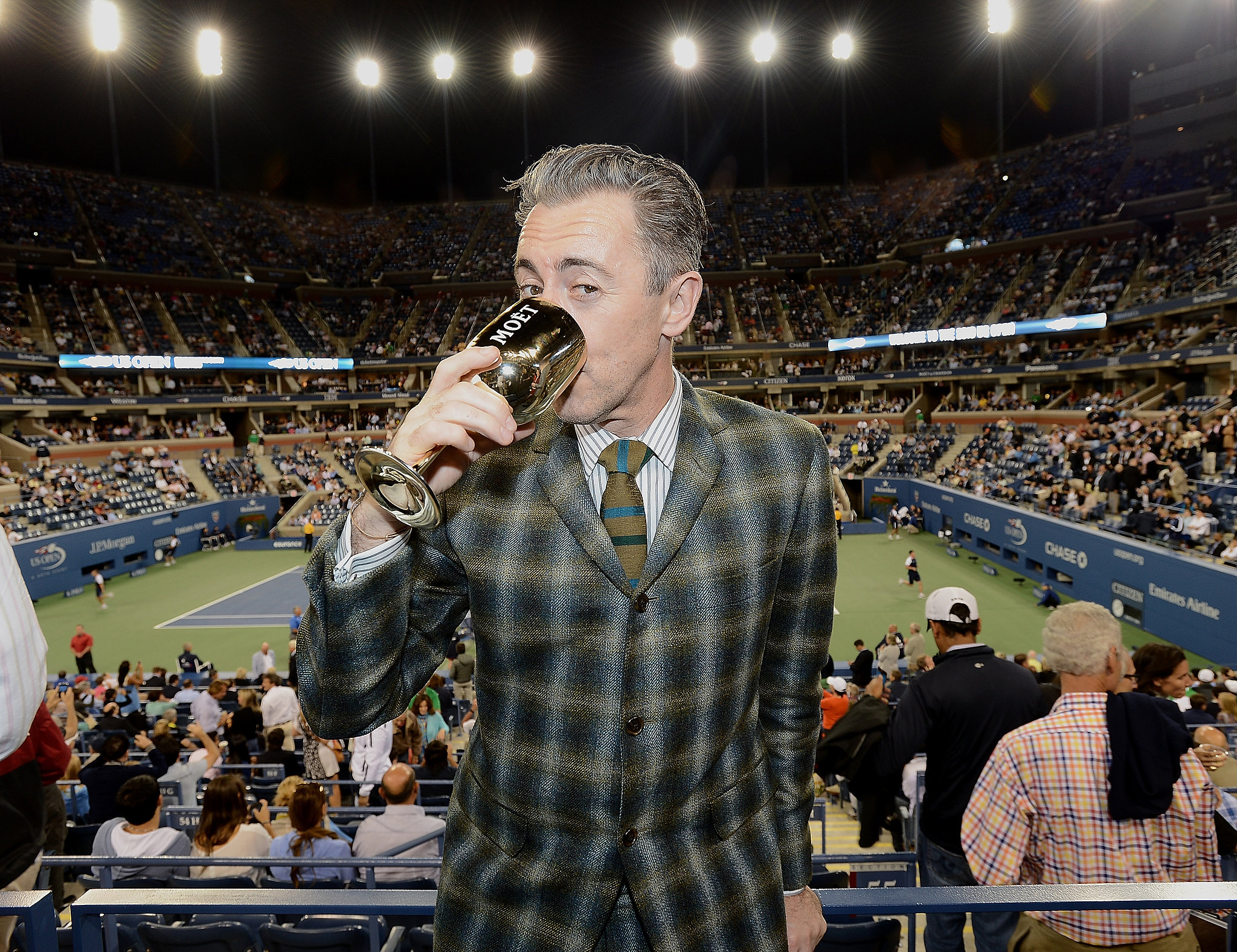Alan Cumming looked dapper in a plaid suit to indulge in a beverage at the US Open.