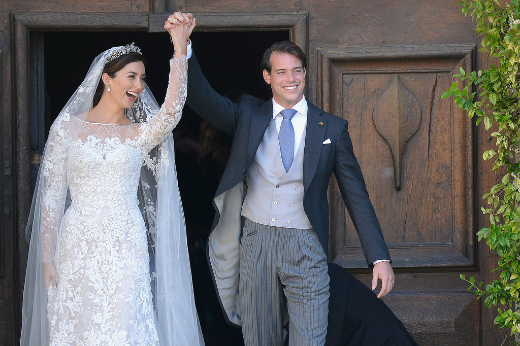 The cute couple raised their hands together after the wedding.