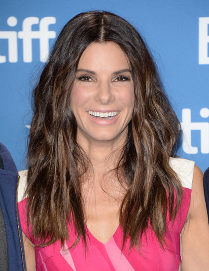At the Gravity press conference in Toronto, Sandra kept things playful with a bright pink dress and glossy beach waves.