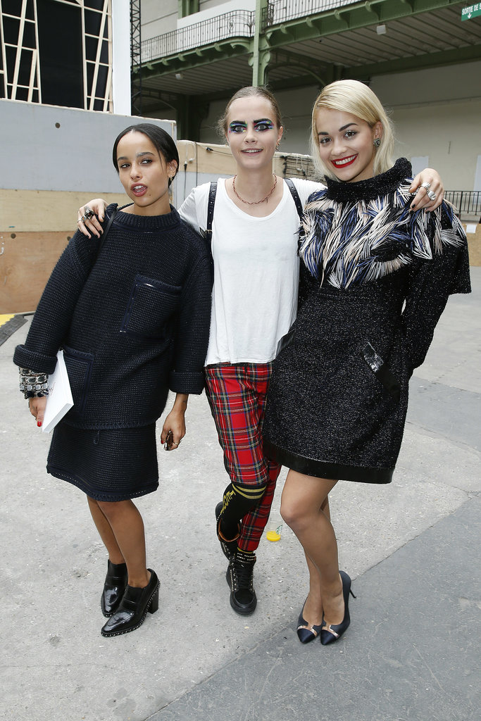 Cara Delevingne — posing here with pals Zoë Kravitz and Rita Ora — rocked Topshop's punky checkered pants with a white tee outside the shows at Paris Fashion Week.