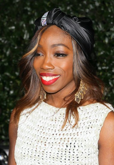 Estelle wore a silky turban with a geometric design, then added a matte red lipstick and lashes to make this into a red-carpet-ready style.