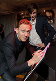 Tom Hiddleston signed a book while Douglas Booth kept watch.