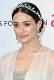 Emmy Rossum took a simple centre-parted hairstyle and made it stunning with the addition of a twisted wire headband with pearls, beads, and sparkle. Matching earrings finished the look.