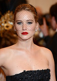 Jennifer Lawrence was the picture of glamour with her veiled headband and red lip at this year's Met Gala.