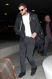 Robert Pattinson caught a late-night flight out of LA in jeans, a sweatshirt, and dark sunglasses.