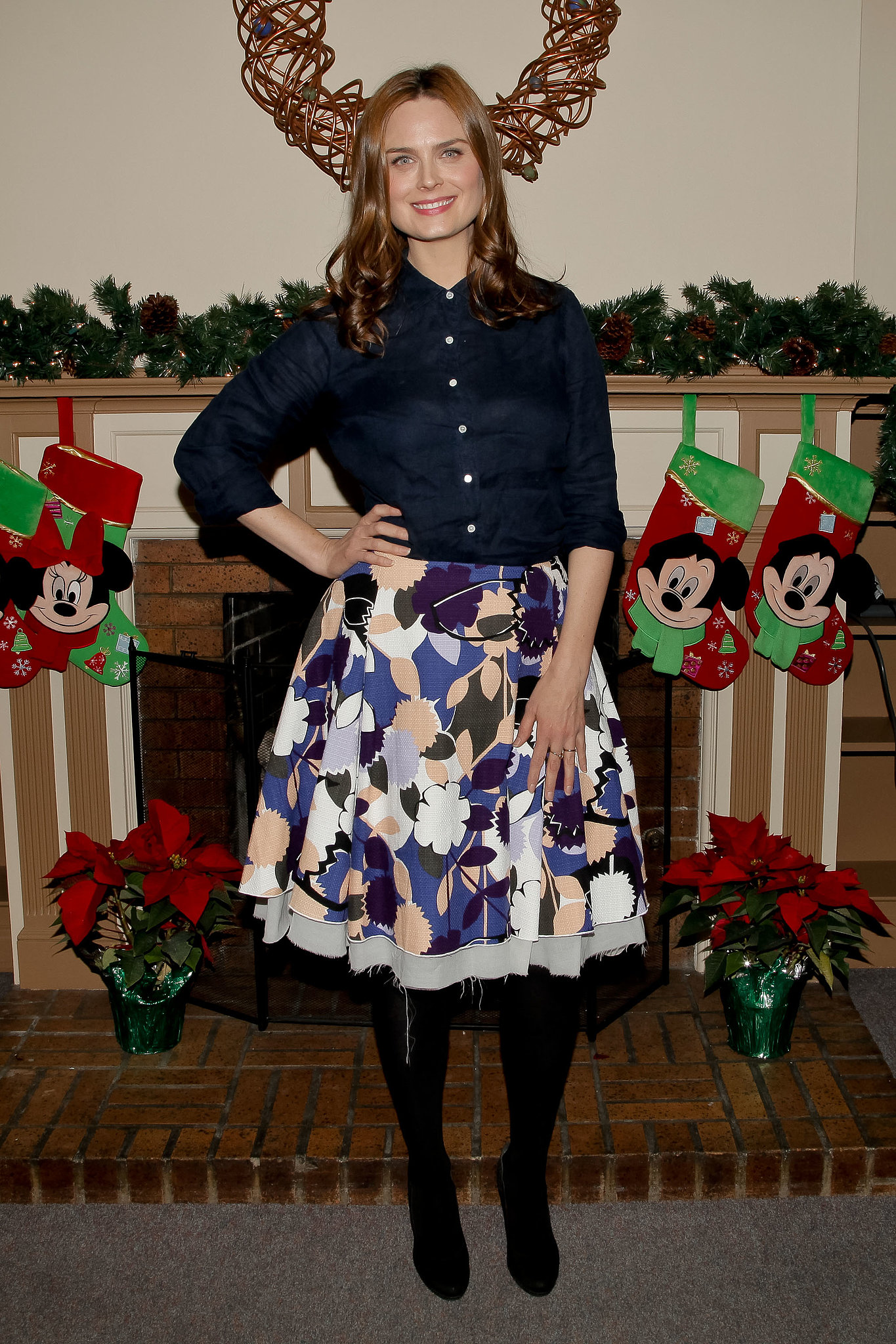 Emily Deschanel posed in front of stockings (hung with care) before reading holiday books to children at Five Acres' holiday open house.