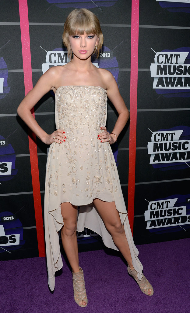 A strapless, sequin-adorned Reem Acra high-low and lace Jimmy Choo booties made up Taylor's CMT Music Awards arrival look.