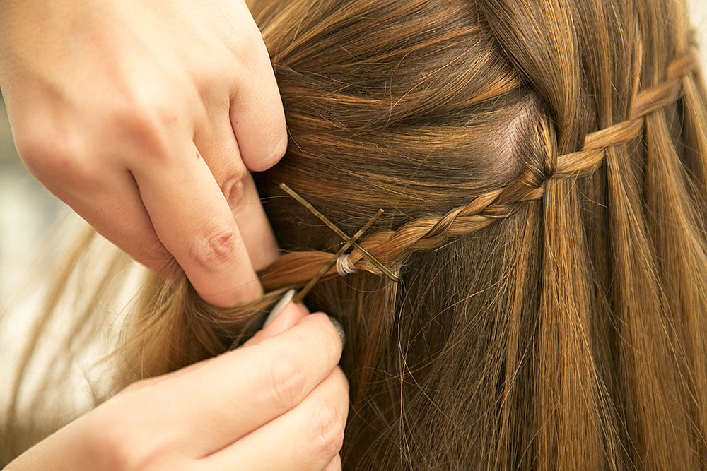 To hide the braided end, tuck it under the layers in the back of your head. Pin it in place by crossing two bobby pins in an X shape. Source: Caroline Voagen Nelson
