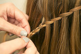 Once you reach the end, extend the woven section of hair with a regular three-strand braid and secure with a clear elastic. Source: Caroline Voagen Nelson