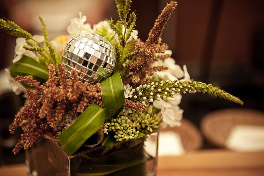 Use mini disco balls for the centerpieces or tie them to the napkins. You can go low-key with just one or group a cluster of them in a vase to up the glam factor. Photo by Melody Davis via Project Wedding
