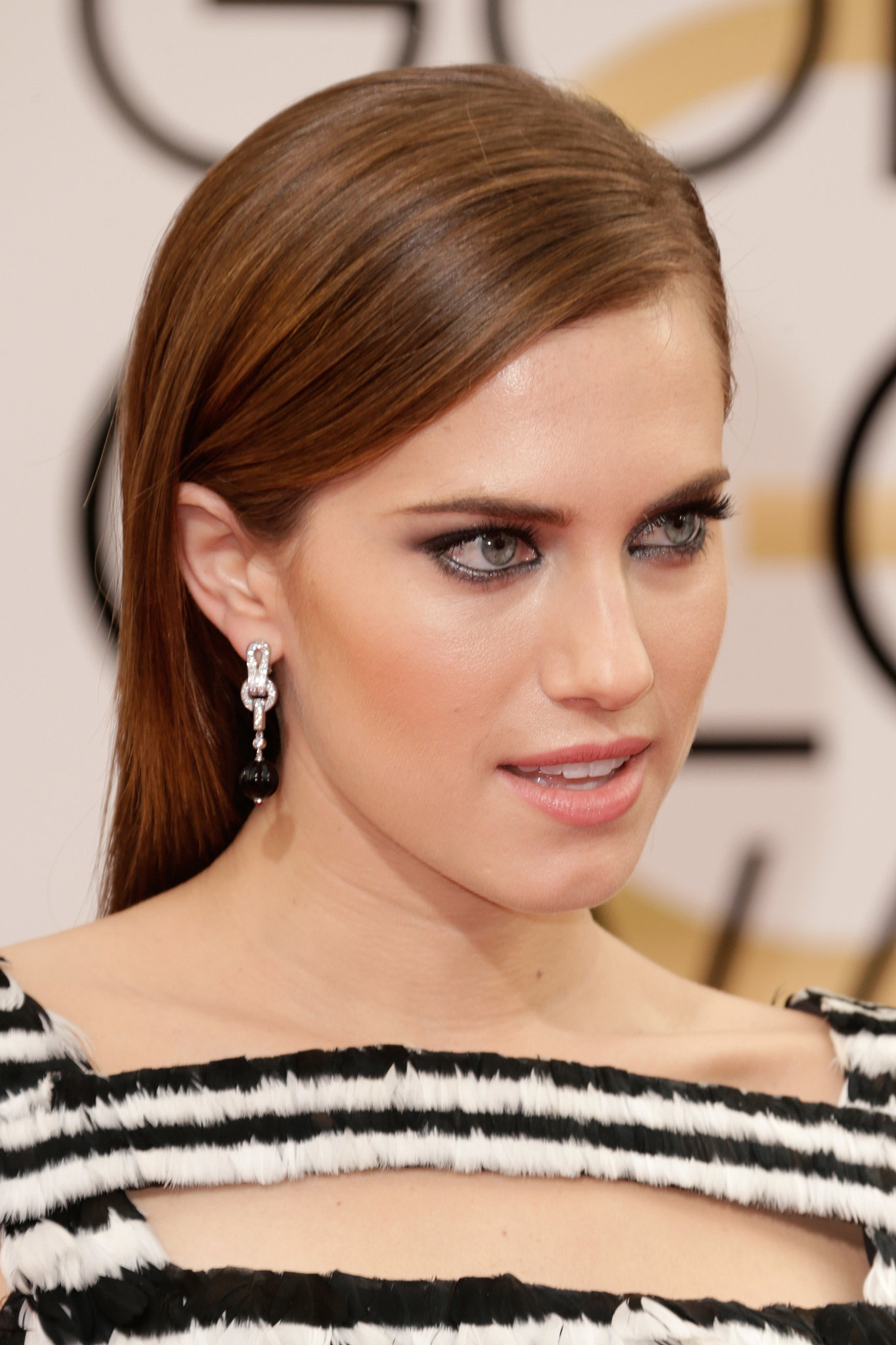 Allison Williams kept her jewels all in the same color family with black and white Cartier Agrafe jewel-drop earrings to complement her gown.