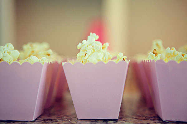 Have a popcorn bar station for guests to add their own seasonings. And mini pink boxes make it even cuter. Photo by Serendipity Studios