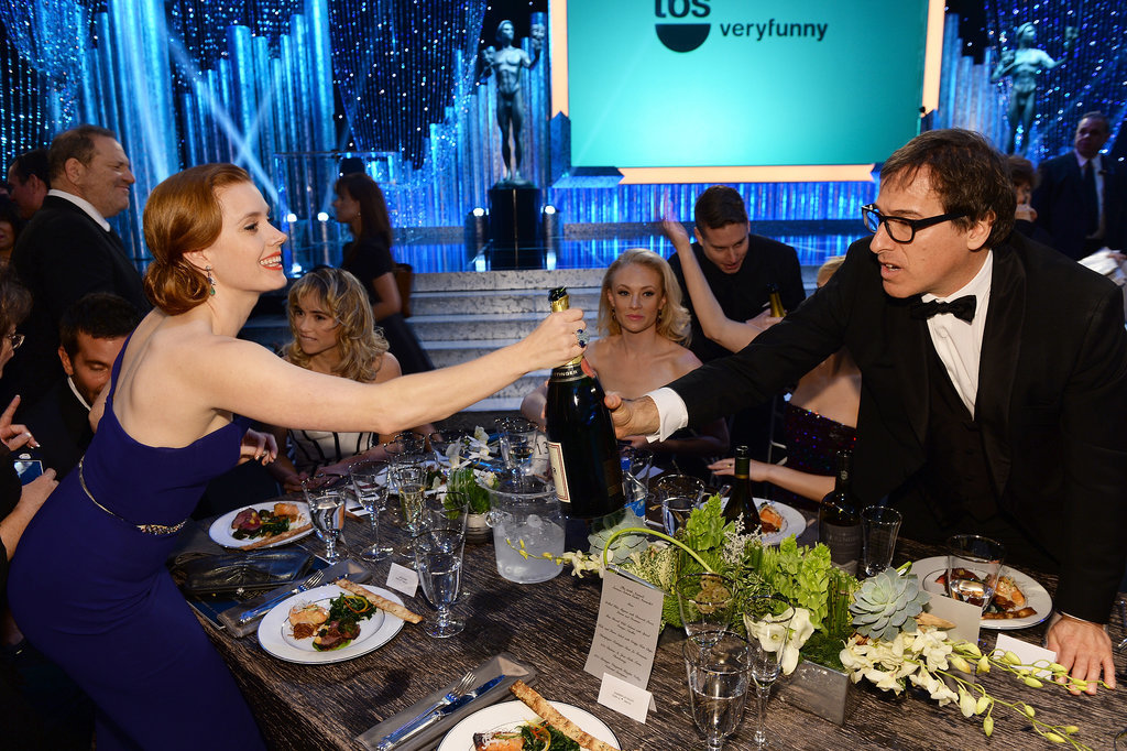 Amy Adams handed off some Champagne to David O. Russell.