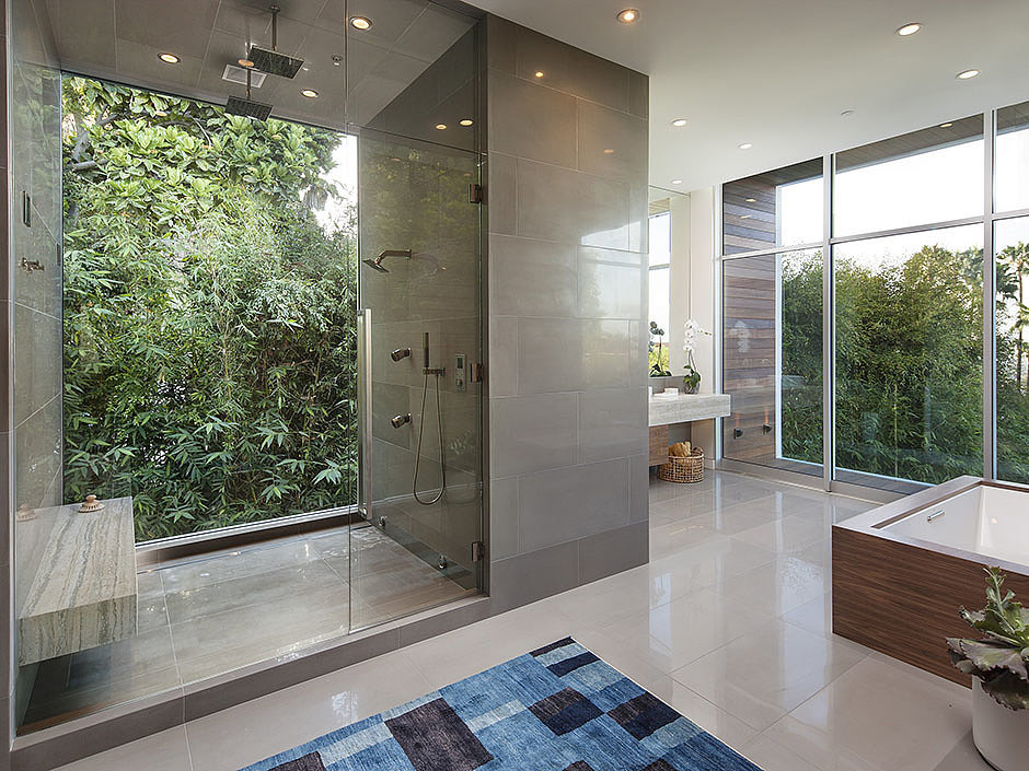 A glass-encased shower makes it easy to gaze at the beautiful greenery while you shower.  Source: The Agency
