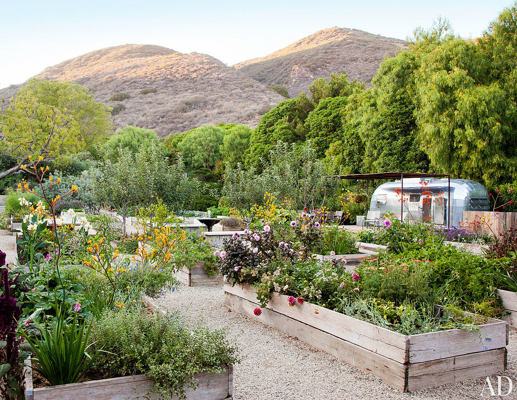 A riding area, created by the previous owners, was converted to a space for one of Jillian's passions: organic gardening. Flowers, herbs, and vegetables thrive in the raised beds, which were constructed from reclaimed scaffolding. Source: Roger Davies via Architectural Digest