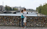 A pair of lovebirds kiss in Paris alongside love padlocks on the Le Pont Des Arts bridge.