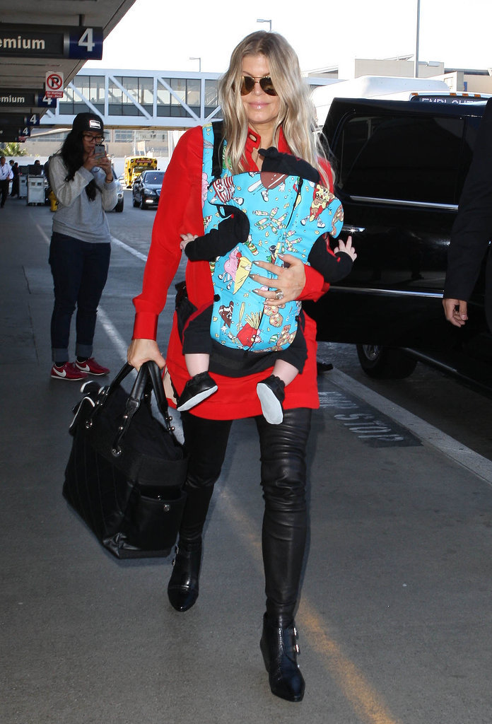 Fergie carried her son, Axl, when she caught a flight out of LAX on Monday.