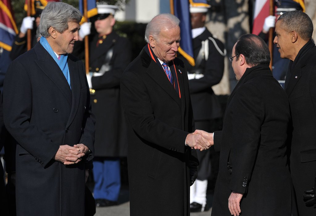 Joe Biden and John Kerry welcomed the French president with handshakes.