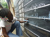 "A young girl in Léogane, Haiti, wrote on a ""Before I Die"" blackboard, where entries from other children included ""to be president"" and ""to make a difference in the lives of others."" Photo courtesy of BeforeIDie.com"