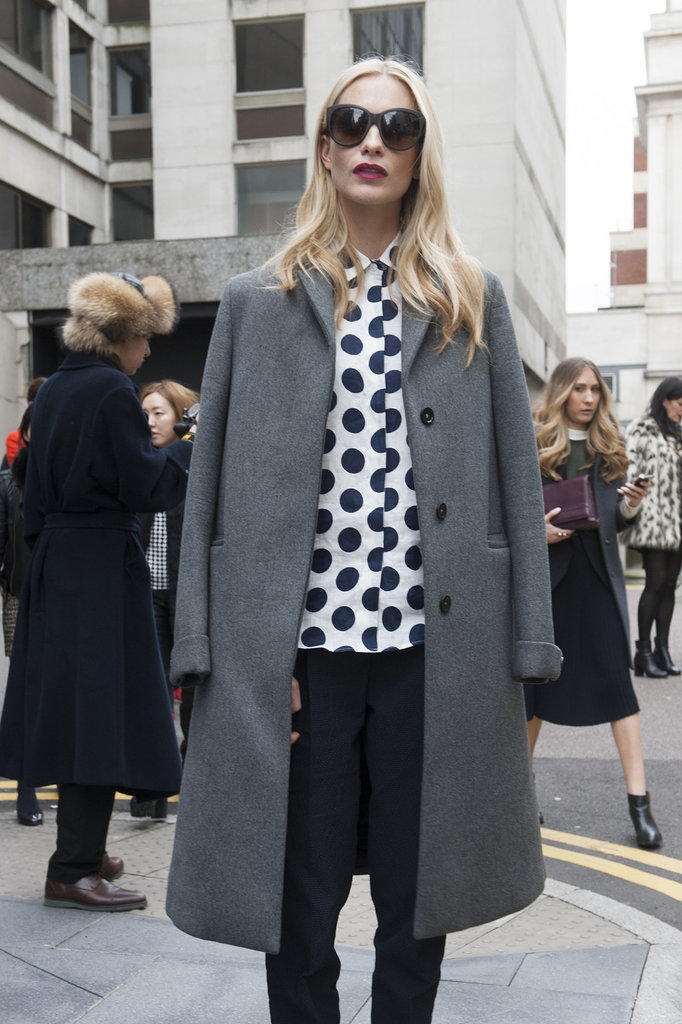 Poppy Delevingne works the polka-dot blouse perfectly with a simple coat and bright lipstick.