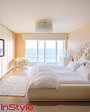 In her guest bedroom (one of two), shades of cream and white contribute to a seamless ocean view. In Kelly fashion, she turned a Medusa sculpture into a headboard and purchased the Murano glass, 1960s chandelier at an auction.  Photo by Dean Kaufman for InStyle