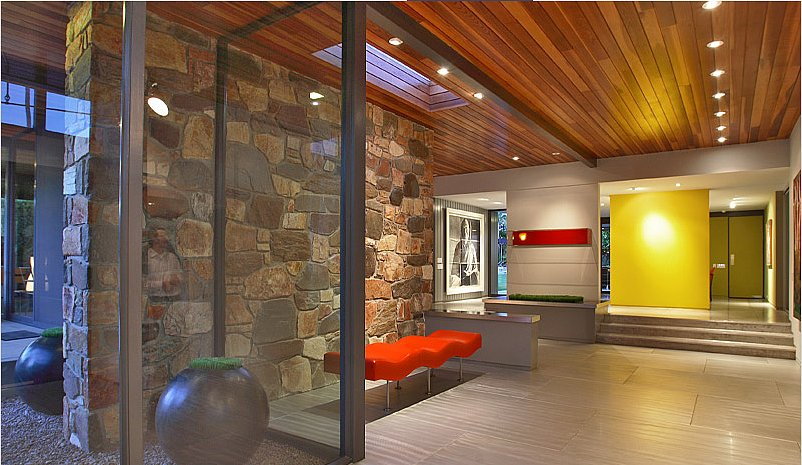 A bright yellow floating wall in the foyer is a nice foil to the wood and stone. Source: Capitas Real Estate