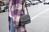 We love the pattern play between her plaid coat and striped bag.