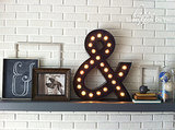I added a few other elements to give my mantel an industrial look; a chalkboard ampersand, an industrial photo that Curt took, a stack of vintage books and a few globes under a glass cloche. Source: Happy Looks Good on You