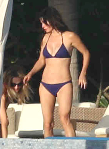 In December 2013, Courteney Cox wore a purple swimsuit in Cabo.