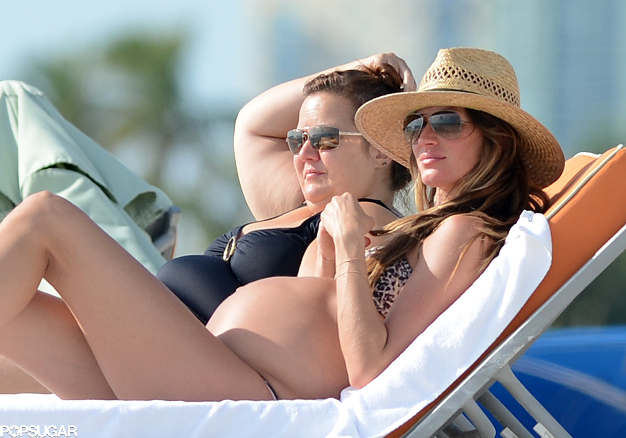 A pregnant Gisele Bundchen tanned on the beach in Miami with a friend in November 2012.