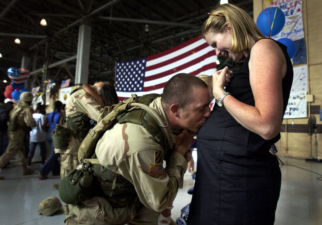 Capt. Tory Burgess of the U.S. Army's 4th Brigade kissed his wife Kathleen's belly on July 16, 2003, at Hunter Army Airfield in Savannah, GA, after returning home from Iraq.