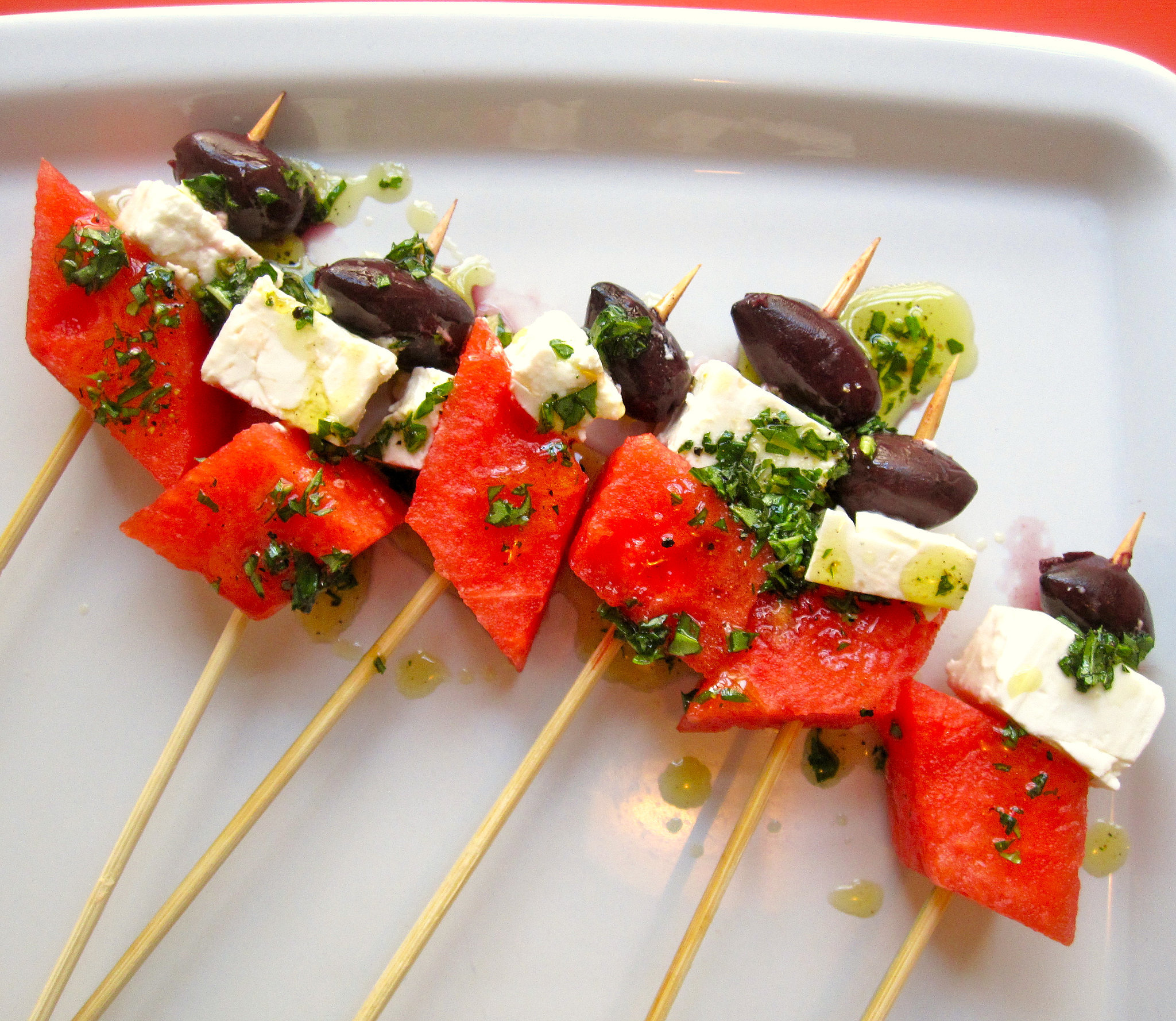 Watermelon, feta, and olive skewers are dressed with mixed herbs and ...