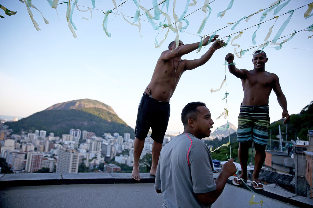 People in Rio de Janeiro put up streamers over their patio to prepare for the World Cup.