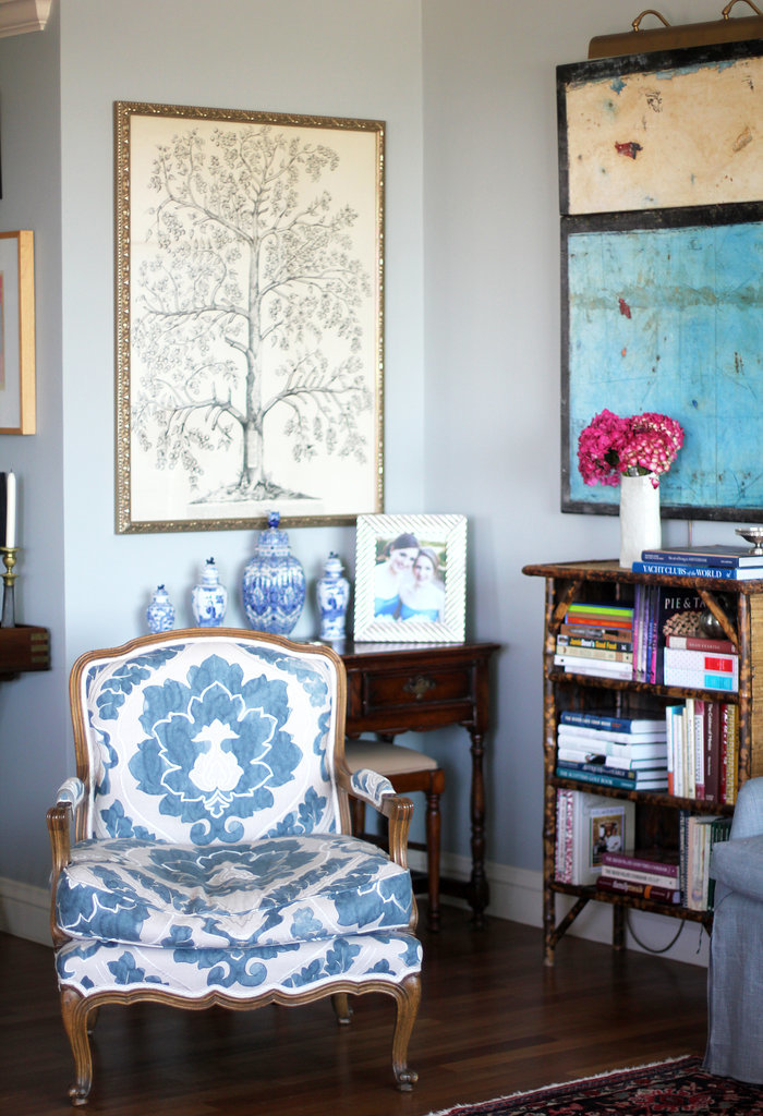 "Like the entryway, each corner is beautifully curated. Here, the color blue ties together a chair reupholstered with Anna French fabric, Asian-style vases, and a Dutch painting. As for her tips on creating a good vignette yourself, she says, ""It does take time to create vignettes so just keep rearranging until you find an interesting balance. Nothing ever stays the same, so have fun changing things around."""