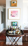 Here's another outstanding example of how various pieces perfectly complement one another. We love how the bright paintings contrast the dark bar stand.