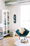 Let's talk about your home! You currently live in a modern apartment in Minneapolis. Tell us about the process you went through while looking for your place. Do you rent or own? How long have you been there?  Joe and I live in the North Loop in a small energy-efficient apartment that boasts a lot of natural light and plenty of modern amenities. The space itself is clean and unassuming, so it doesn't really compete with our decor choices. I love the open floor plan, and our floor-to-ceiling windows are incredible, but I do miss the character that comes with an older building. We're renting at the moment, but we're in the process of deciding where to settle for the next couple of years. Source: Melissa Oholendt for The Everygirl