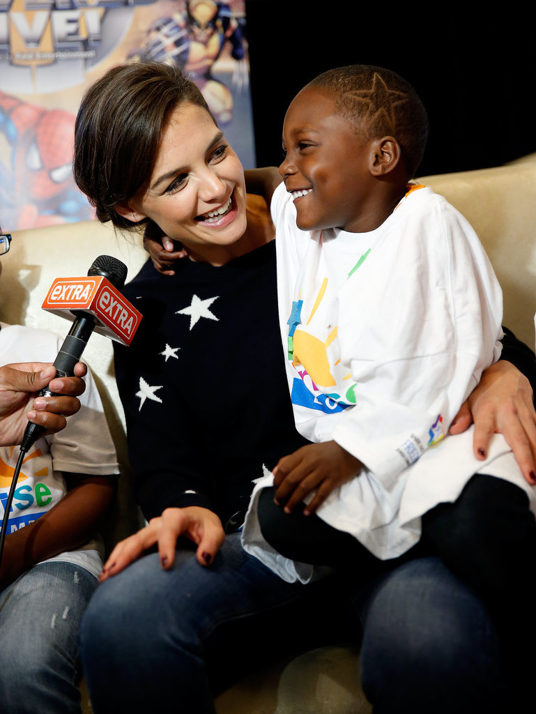 On Wednesday, Katie Holmes couldn't help smile while holding a sweet kid at the Marvel Universe Live! premiere in NYC, where children with cancer from Sunrise Day Camp got some one-on-one time with the star.