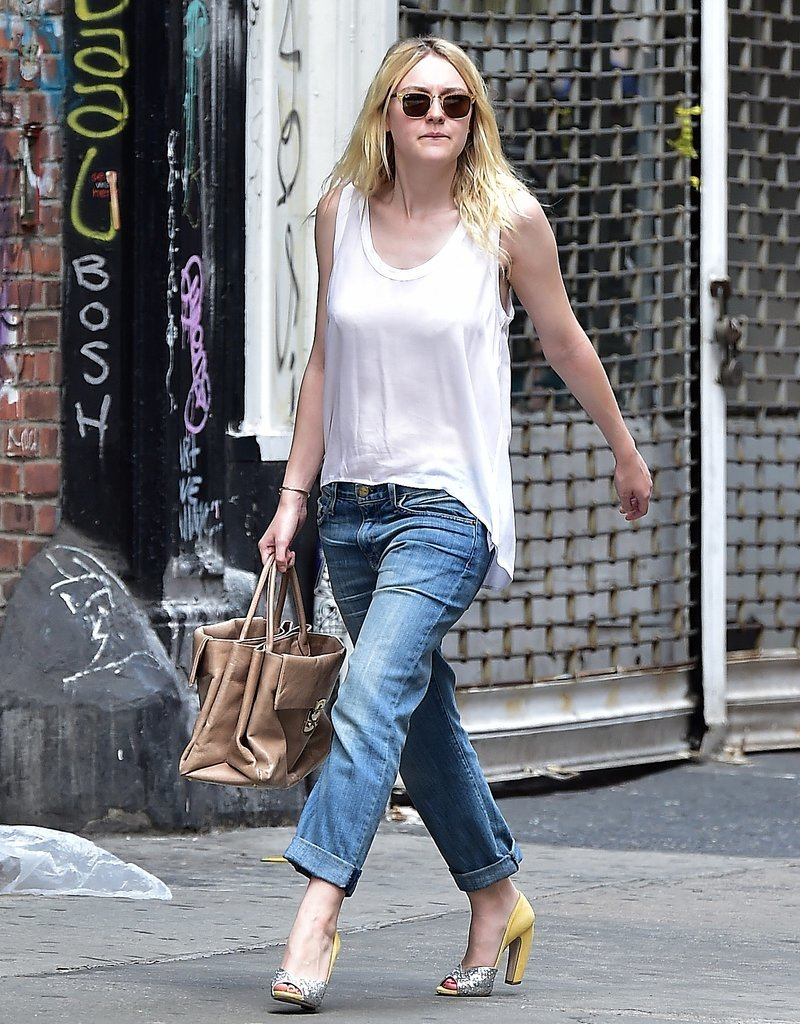 Dakota opted for a pair of slouchy Current/Elliott The Fling jeans, which she double cuffed, and a white, loose-fitting high-low top. Her accessories included a tan leather top-handle bag and mat