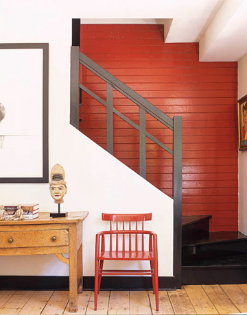 A brick-red wall color and coordinating chair add a sense of warmth and comfort to this entry. Source
