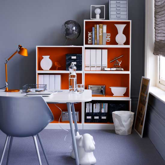 This gray-lavender office is given a wake-up call thanks to the orange shelving unit. Source