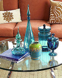 Cool-colored accents can work well with warmer-colored pieces. This collection of blue and turquoise objects is a nice contrast to the warm, red-toned sofa in the background.  Source