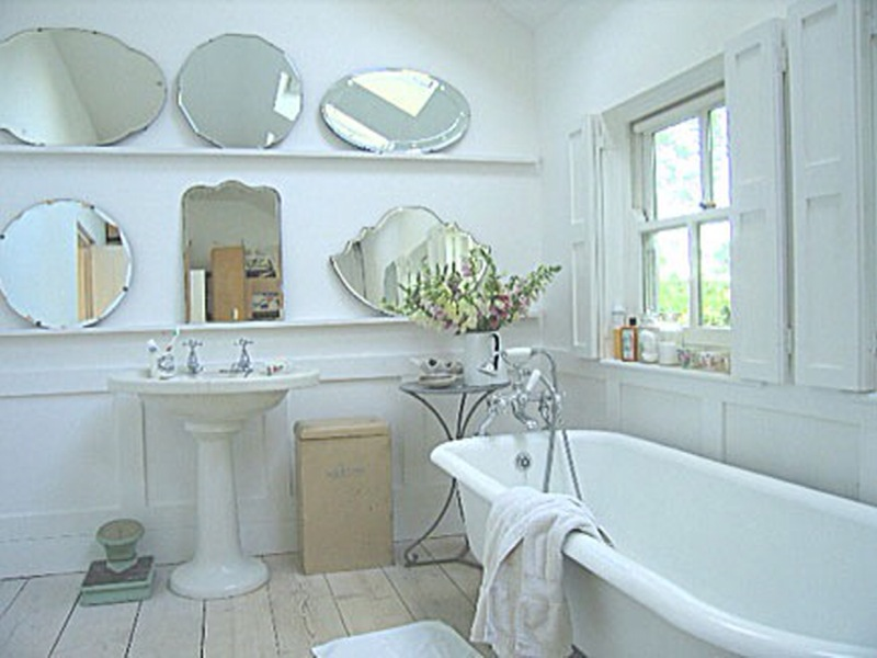 Two shelves host an arrangement of mirrors that reflect light beautifully in this bright bathroom. Source