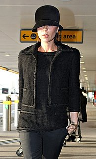 Victoria Beckham in Black Tweed Jacket and Hat at Heathrow Airport in London