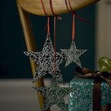 Dress your dinner chairs with ornaments. Just make sure not to hang breakable ones! Source