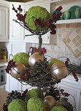 Use osage orange as an element in a seasonal table display. I love the way the colors mix with the pearly bulbs and red berries.  Source